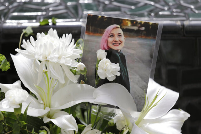 A photo of Summer Taylor, who suffered critical injuries and died after being hit by a car while protesting over the weekend, sits among flowers at the King County Correctional Facility where a hearing was held for the suspect in their death Monday, July 6, 2020, in Seattle. Dawit Kelete is accused of driving a car on to a closed Seattle freeway and hitting two protesters, killing one, over the weekend. Seattle has been the site of prolonged unrest over the death of George Floyd, a Black man who was in police custody in Minneapolis, and had shut down the interstate for 19 days in a row. (AP Photo/Elaine Thompson)