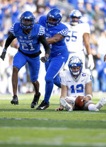 Kentucky cornerback Chris Westry (21) and defensive tackle Kordell Looney (59) celebrate after sacking Middle Tennessee quarterback Brent Stockstill (12) during the second half of an NCAA college football game in Lexington, Ky., Saturday, Nov. 17, 2018. (AP Photo/Bryan Woolston)