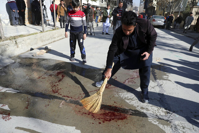 An Afghan man sweeps blood after Gunmen fired in Kabul, Afghanistan, Sunday, Jan. 17, 2021. Gunmen fired on a car in northern Kabul on Sunday, killing two women judges who worked for Afghanistan's high court and wounding the driver, a court official said. It was the latest attack in the Afghan capital during peace talks between Taliban and Afghan government officials in Qatar. (AP Photo/Rahmat Gul)