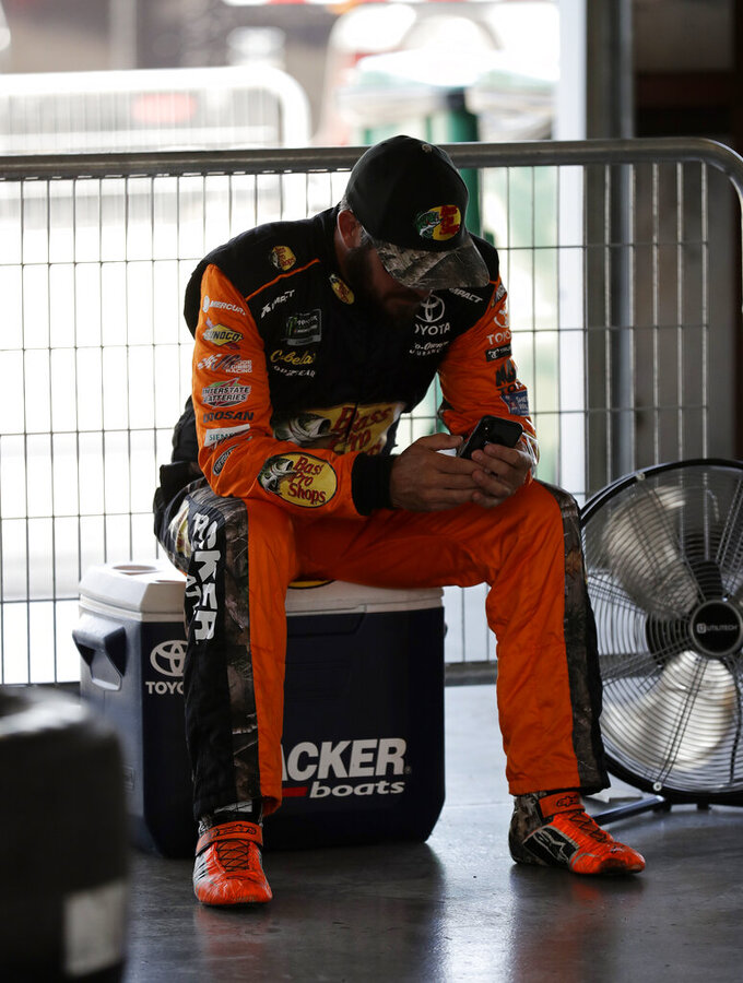 Martin Truex Jr., checks his phone during a practice for the NASCAR Sprint Cup Series auto race at Chicagoland Speedway in Joliet, Ill., Saturday, June 29, 2018. (AP Photo/Nam Y. Huh)