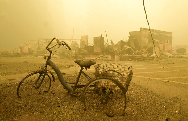 FILE - In this Sept. 11, 2020 file photo a trike stands near the burnt remains of a building destroyed by a wildfire near the Lake Detroit Market in Detroit, Ore. The blaze was one of multiple fires that burned across the state last month. Three Pacific Northwest law firms have filed a class action lawsuit against Pacific Power and its parent company, Portland-based PacifiCorp, alleging that the power company failed to shut down its power lines despite a historic wind event and extremely dangerous wildfire conditions. (Mark Ylen/Albany Democrat-Herald via AP, File)