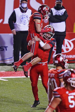 Utah wide receiver Britain Covey (18) jumps in to the arms of quarterback Jake Bentley (8) after he scored against Oregon State during the second half of an NCAA college football game Saturday, Dec. 5, 2020, in Salt Lake City. (AP Photo/Rick Bowmer)