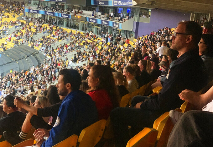 Thousands of people attend a concert by the band Six60 on Saturday, Feb 13, 2021, in Wellington, New Zealand. New Zealand's largest city of Auckland is being placed into a three-day lockdown Sunday following the discovery of three unexplained virus cases. (AP Photo/Nick Perry)