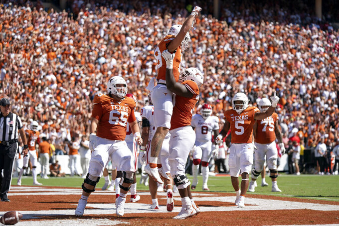 Texas tight end Jared Wiley (18) is lifted up by Texas offensive lineman Christian Jones (70) after making a touchdown catch during the first half of an NCAA college football game against Oklahoma at the Cotton Bowl, Saturday, Oct. 9, 2021, in Dallas. (AP Photo/Jeffrey McWhorter)