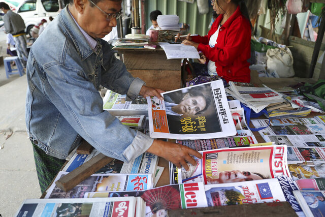 A man looks through newspapers with front pages leading with Myanmar leader Aung San Suu Kyi at the International Court of Justice hearing, near a roadside journal shop Thursday, Dec. 12, 2019, in Yangon, Myanmar. Suu Kyi testified to the court that the exodus of hundreds of thousands of Rohingya Muslims to neighboring Bangladesh was the unfortunate result of a battle with insurgents. She denied that the army had killed civilians, raped women and torched houses. (AP Photo/Thein Zaw)