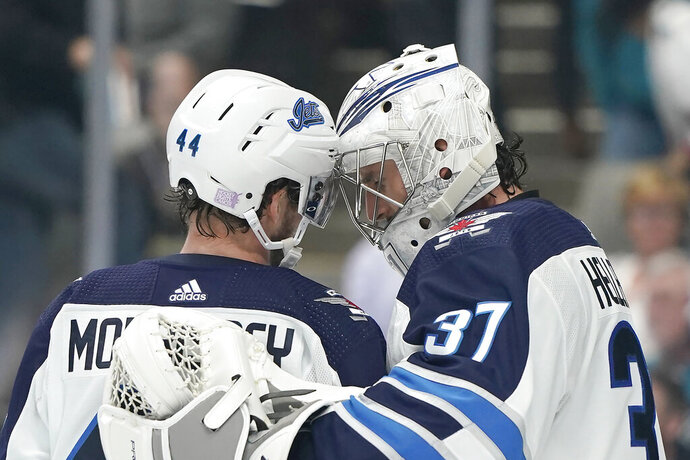 Winnipeg Jets goaltender Connor Hellebuyck (37) is congratulated by Josh Morrissey (44) after the team's 3-2 victory over the San Jose Sharks in an NHL hockey game in San Jose, Calif., Friday, Nov. 1, 2019. (AP Photo/Tony Avelar)