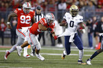 Akron quarterback DJ Irons (0) cuts upfield while pursued by Ohio State defensive lineman Haskell Garrett (92) and linebacker Cody Simon (30) during the first half of an NCAA college football game Saturday, Sept. 25, 2021, in Columbus, Ohio. (AP Photo/Jay LaPrete)
