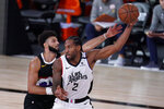 Los Angeles Clippers' Kawhi Leonard (2) is defended by Denver Nuggets' Jamal Murray (27) during the second half of an NBA conference semifinal playoff basketball game, Wednesday, Sept. 9, 2020, in Lake Buena Vista, Fla. (AP Photo/Mark J. Terrill)