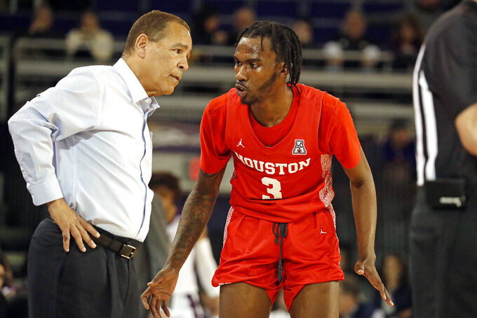 Houston coach Kelvin Sampson talks with DeJon Jarreau during the second half of the team's NCAA college basketball game against the East Carolina in Greenville, N.C., Wednesday, Jan. 29, 2020. (AP Photo/Karl B DeBlaker)