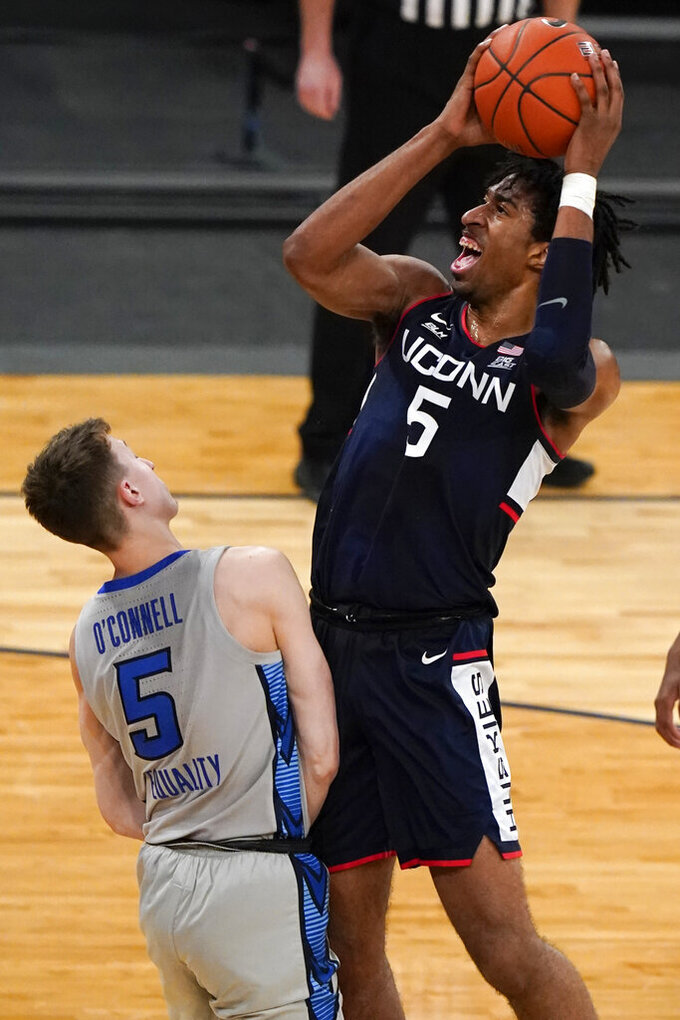 Connecticut's Isaiah Whaley (5) shoots over Creighton's Alex O'Connell (5) during the first half of an NCAA college basketball game in the semifinals in the Big East men's tournament Friday, March 12, 2021, in New York. (AP Photo/Frank Franklin II)