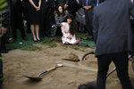 FILE - In this April 29, 2019, file, photo, Hannah Kaye, center, the daughter of Lori Kaye, who died when a man opened fire during Passover service inside a synagogue, sits on the ground with her aunt, Randi Grossman, as the last shovels of dirt cover her mother's grave during funeral services, in San Diego. Israeli researchers reported Wednesday, May 1, 2019, that violent attacks against Jews spiked significantly last year, with the largest reported number of Jews killed in anti-Semitic acts in decades, leading to an