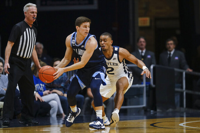 Villanova guard Collin Gillespie, left, looks to pass the ball around Butler guard Aaron Thompson (2) during the first half of an NCAA college basketball game in Indianapolis, Wednesday, Feb. 5, 2020. (AP Photo/AJ Mast)