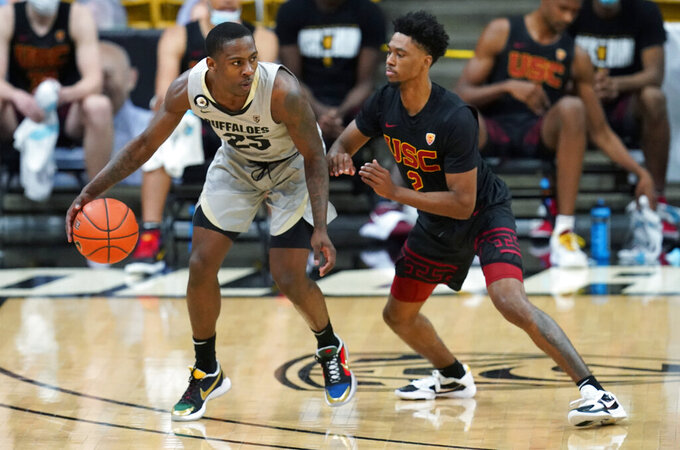 Colorado guard McKinley Wright IV, left, looks to pass the ball as Southern California guard Tahj Eaddy defends during the first half of an NCAA college basketball game Thursday, Feb. 25, 2021, in Boulder, Colo. (AP Photo/David Zalubowski)