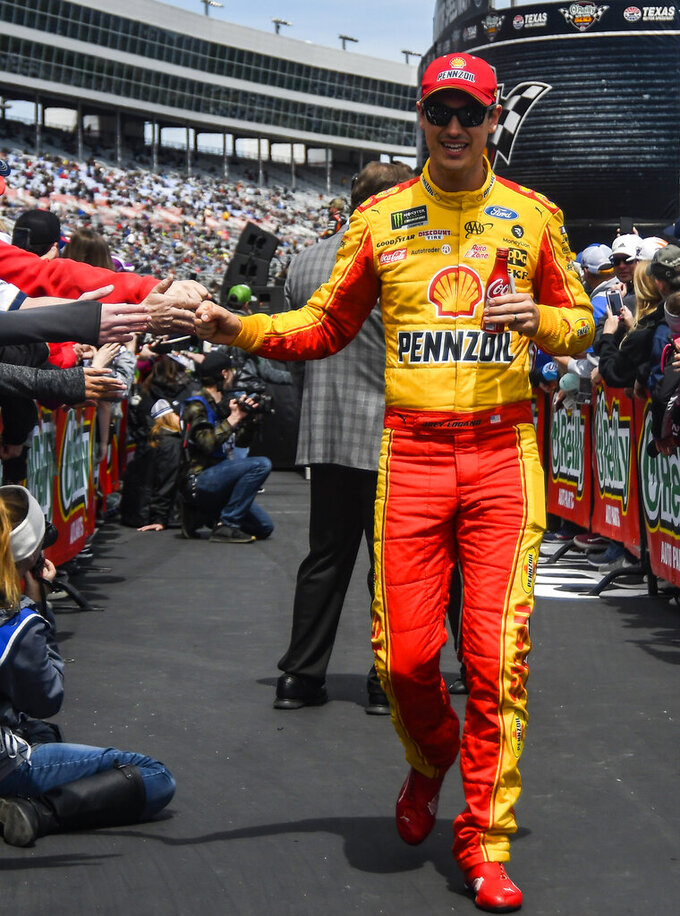 Driver Joey Logano fist bumps fans before a NASCAR Cup auto race at Texas Motor Speedway, Sunday, March 31, 2019, in Fort Worth, Texas. (AP Photo/Randy Holt)