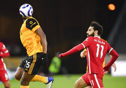 Wolverhampton Wanderers' Willy Boly, left, heads the ball away from Liverpool's Mohamed Salah during the English Premier League soccer match between Wolverhampton Wanderers and Liverpool at Molineux Stadium in Wolverhampton, England, Monday, March. 15, 2021. (AP Photo/Paul Ellis,Pool)