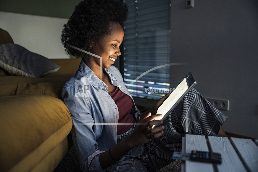 Woman smiling while using digital tablet in living room