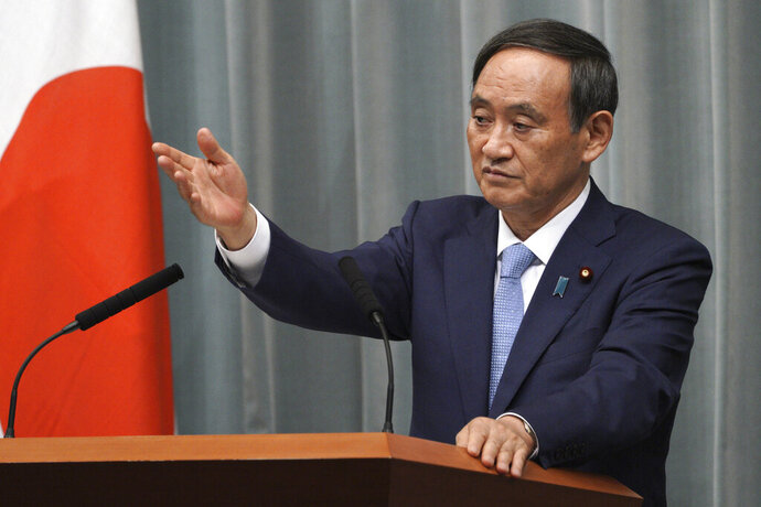 FILE - In this Sept. 11, 2019, file photo, Yoshihide Suga, Chief Cabinet Secretary speaks during a press conference at the prime minister's official residence in Tokyo. Chief Cabinet Secretary Suga told reporters that a Japanese fisheries inspection ship received a distress call from another North Korean boat of the capsizing. He said the Japanese fisheries and coast guard patrol boats are jointly searching for the missing. (AP Photo/Eugene Hoshiko, File)