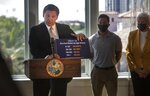 Gov.  Ron DeSantis shows a card stating COVID-19 survival rates by age group as he announces phase three openings at news conference in St. Petersburg, Fla., on Friday, Sept. 25, 2020.  DeSantis lifted all restrictions on restaurants and other businesses in Florida on Friday in a move to reopen the state's economy despite the spread of the coronavirus. (John Pendygraft/Tampa Bay Times via AP)