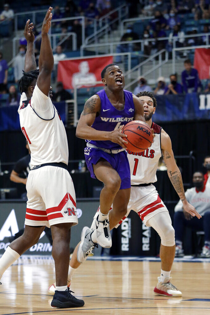 Abilene Christian guard Damien Daniels goes to the basket between Nicholls State guard Ty Gordon, left, and forward Jaylen Fornes (1) during the first half of an NCAA college basketball game for the Southland Conference men's tournament championship Saturday, March 13, 2021, in Katy, Texas. (AP Photo/Michael Wyke)