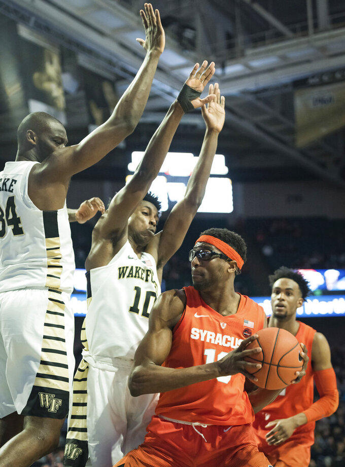 Syracuse center Paschal Chukwu (13) is pressured by Wake Forest forwards Sunday Okeke (34) and Jaylen Hoard (10) during the second half of an NCAA college basketball game, Saturday, March 2, 2019, at Joel Coliseum in Winston-Salem, N.C. (Allison Lee Isley/The Winston-Salem Journal via AP)