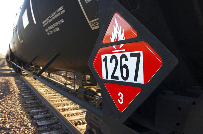 FILE - This Nov. 6, 2013, file photo, shows a warning placard on a tank car carrying crude oil near a loading terminal in Trenton, N.D. North Dakota officials are pressuring the state of Washington to back off from legislation requiring oil shipped by rail to have more of its volatile gases removed. Proponents of the bill awaiting Gov. Jay Inslee's signature say it will boost safety, but North Dakota officials worry it could hamper the nation's No. 2 oil producer. North Dakota's three members of Congress have asked Inslee to veto the bill. North Dakota regulators are considering a lawsuit. (AP Photo/Matthew Brown, File)