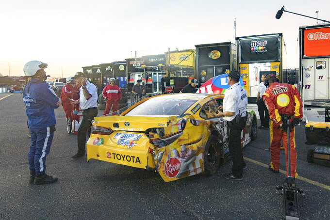 Officials and crew members gather around a car after Kyle Busch pulled out of the pit and parked next to his team's hauler during a NASCAR Cup Series auto race Sunday, Sept. 5, 2021, in Darlington, S.C. (AP Photo/John Amis)