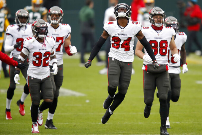 Tampa Bay Buccaneers run out onto the field for warm ups before the NFC championship NFL football game against the Green Bay Packers in Green Bay, Wis., Sunday, Jan. 24, 2021. (AP Photo/Matt Ludtke)