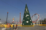 In this Thursday, Dec. 5, 2019 photo, people walk near a large Christmas tree in al-Zawra Park, Baghdad, Iraq. Leaders of Iraq's Christians unanimously cancelled Christmas-related celebrations in solidarity with the protest movement - but the aims of their stance go deeper than tinsel and fairy lights. In the slogans calling for a united Iraq, Christians see hope for much needed change from a sectarian system that has long marginalized them. (AP Photo/Khalid Mohammed)