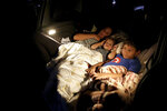 Ana Paula Santos and her children watch a movie from inside their car at a drive-in movie theater where drivers must leave one space empty between them in Brasilia, Brazil, Wednesday, May 13, 2020. The drive-in offers three shows per day, with a children's movie followed by two features for adults. (AP Photo/Eraldo Peres)