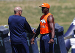 Retired NFL defensive standout DeMarcus Ware, right, confers with Denver Broncos defensive line coach Bill Kollar during drills at the NFL football team's training camp Wednesday, June 13, 2018, in Englewood, Colo. (AP Photo/David Zalubowski)