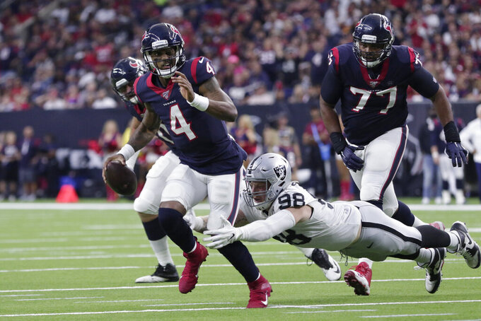 Houston Texans quarterback Deshaun Watson (4) is pressured by Oakland Raiders defensive end Maxx Crosby (98) as he looks to make a pass for a touchdown to tight end Darren Fells during the second half of an NFL football game Sunday, Oct. 27, 2019, in Houston. (AP Photo/Michael Wyke)