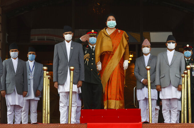 Nepalese president Bidhya Devi Bhandari wearing face mask inspects a guard of honer at parliament in Kathmandu, Nepal, Friday, May 15, 2020. Bhandari presented the government's policies and programs for the upcoming fiscal year on Friday. (AP Photo/Niranjan Shrestha)