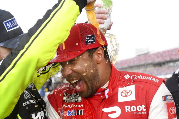 Bubba Wallace is dowsed by Ryan Blaney after winning a NASCAR Cup series auto race Monday, Oct. 4, 2021, in Talladega, Ala. (AP Photo/John Amis)