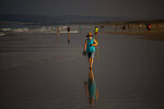 A woman wearing a face mask walks at the beach in Zahara de los Atunes, Cadiz province, south of Spain, on Saturday, July 25, 2020. Ministers are set to remove Spain from the Government's list of safe countries to travel to after the European country saw a rise in Covid-19 cases. The decision means those coming back from Spain will have to self-isolate for two weeks upon their return to England. (AP Photo/Emilio Morenatti)