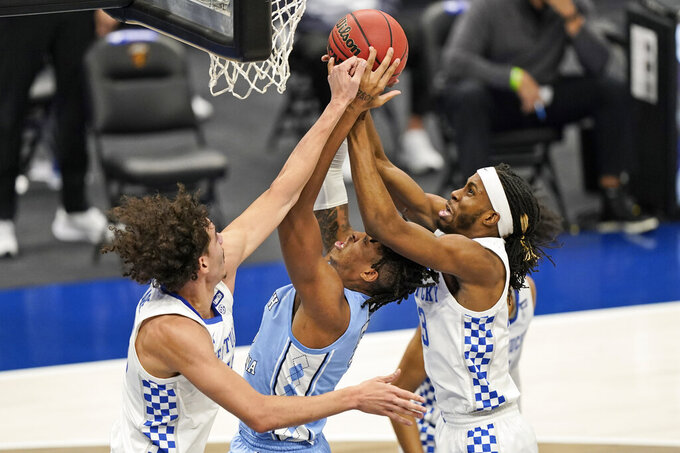 Kentucky's Lance Ware, left, and Kentucky's Isaiah Jackson, right, put pressure on North Carolina's Armando Bacot, center, the first half of an NCAA college basketball game, Saturday, Dec. 19, 2020, in Cleveland. (AP Photo/Tony Dejak)
