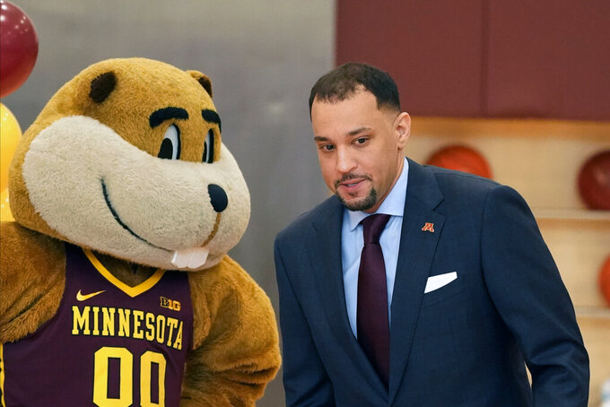 New University of Minnesota mens' head basketball coach Ben Johnson walks past university mascot Goldy Gopher after he met the media Tuesday, March 23, 2021, in Minneapolis. Johnson replaces Richard Pitino, who was fired after eight seasons and took the job at New Mexico.  (AP Photo/Jim Mone)