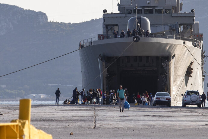 Migrants wait outside a military vessel after their disembarkation at the port of Elefsina, near Athens, on Saturday, Nov. 2, 2019. The transfer of migrants from overcrowded camps on the islands to the Greek mainland continued this weekend, with 415 arriving Saturday afternoon at the port of Elefsina west of Athens and at least another 400 expected Sunday or early Monday. (AP Photo/Yorgos Karahalis)