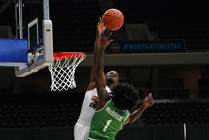 Western Kentucky guard Josh Anderson blocks a shot by North Texas guard Mardrez McBride (1) during the first half of the championship game in the NCAA Conference USA men's basketball tournament Saturday, March 13, 2021, in Frisco, Texas. (AP Photo/Tony Gutierrez)