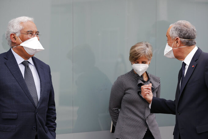 Portuguese President Marcelo Rebelo de Sousa, right, talks to Prime Minister Antonio Costa, left, and Health Minister Marta Temido, center, at the end of a visit to the hospital in Lisbon, Tuesday, Jan. 26, 2021. Portugal's government is showing signs of strain as the country reels from almost two weeks at the top of the world rankings of daily new COVID-19 cases and deaths by size of population. (AP Photo/Armando Franca)