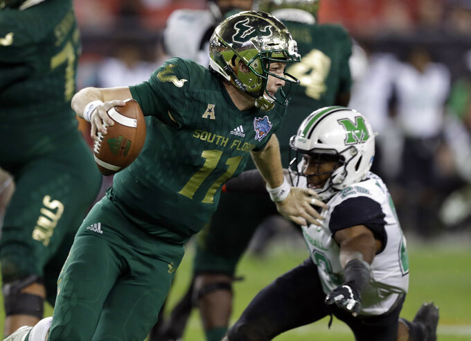 South Florida quarterback Blake Barnett (11) eludes a tackle by Marshall safety Malik Gant (29) during the second half of the Gasparilla Bowl NCAA college football game Thursday, Dec. 20, 2018, in Tampa, Fla. (AP Photo/Chris O'Meara)