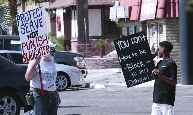 Rick Bramhall, left, and Giovanni Robinson hold up signs Monday, June 1, 2020, in Yuma, Ariz., during an