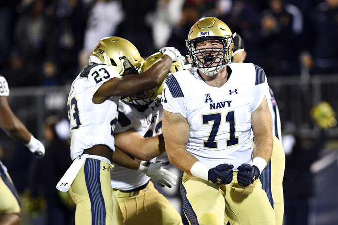 Navy offensive tackle Billy Honaker (71) screams after wide receiver Mychal Cooper scored during the first half of an NCAA college football game against Connecticut on Friday, Nov. 1, 2019, in East Hartford, Conn. (AP Photo/Stephen Dunn)