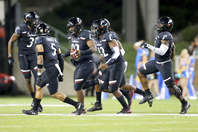 Cincinnati defensive tackle Curtis Brooks (92) jogs back to the sideline after a fumble recovery during the second half of the team's NCAA college football game against UCLA on Thursday, Aug. 29, 2019, in Cincinnati. (Kareem Elgazzar/The Cincinnati Enquirer via AP)