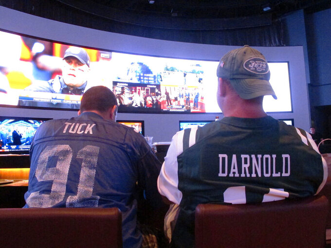 This Sept. 9, 2018 photo shows fans of the New York Giants and Jets watching a football game after placing bets in the sports betting lounge at the Ocean Casino Resort in Atlantic City, N.J. The coronavirus outbreak has added new wrinkles for bettors this year, but even so, the nation's sports books expect a record year of bets on football in 2020 from an antsy public that has been cooped up for months amid the pandemic. (AP Photo/Wayne Parry)