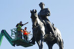 FILE - In this Monday June 8, 2020 file photo a crew from the Virginia Department of General Services inspect the statue of Confederate Gen. Robert E. Lee on Monument Avenue in Richmond, Va. If a court clears the way for the state of Virginia to take down one of the country's most prominent Confederate statues, contractors will also be removing something else from the enormous monument: a 134-year-old time capsule rumored to contain a valuable and historically significant photo of deceased President Abraham Lincoln. (AP Photo/Steve Helber)