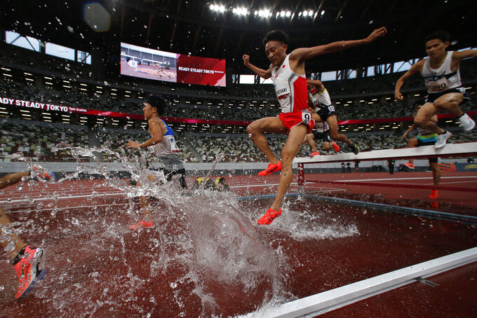 FILE - In this May 9, 2021, file photo, Japanese athletes competes the men's 3,000-meter steeplechase during an athletics test event for Tokyo 2020 Olympics Games at National Stadium in Tokyo. IOC officials say the Tokyo Olympics will open on July 23 and almost nothing now can stop the games from going forward. (AP Photo/Shuji Kajiyama, File)