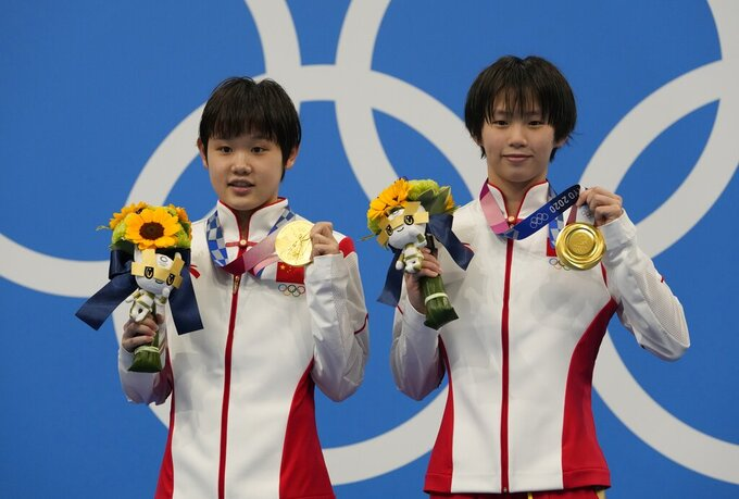 Yuxi Chen and Jiaqi Zhang of China pose for a photo after winning gold medals during the women's synchronized 10m platform diving final at the Tokyo Aquatics Centre at the 2020 Summer Olympics, Tuesday, July 27, 2021, in Tokyo, Japan. (AP Photo/Dmitri Lovetsky)