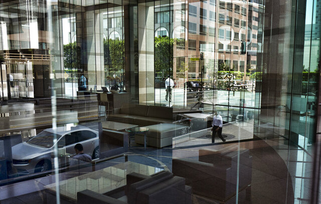 FILE - In this Aug. 27, 2018, file photo downtown Los Angeles buildings and officer workers are reflected in the front windows by a bank. When applying for a personal loan, some lenders may ask you for information that isn't on your credit report. In some cases, information like where you live, where you went to school and your major are taken into account. (AP Photo/Richard Vogel, File)
