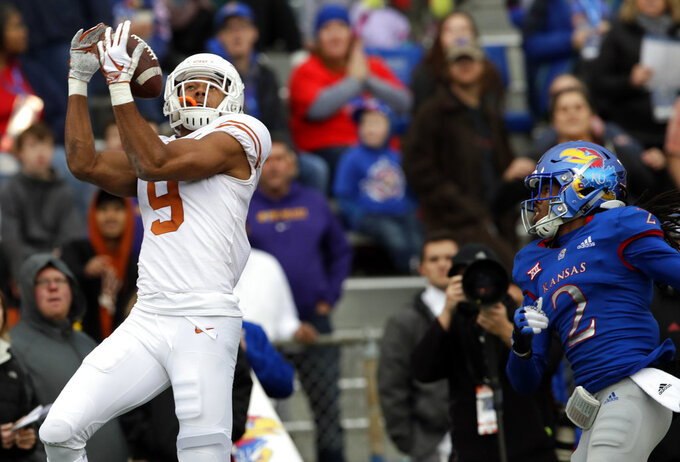 Texas wide receiver Collin Johnson (9) catches a Sam Ehlinger pass for a touchdown in front of Kansas cornerback Corione Harris (2) during the first half of an NCAA college football game in Lawrence, Kan., Friday, Nov. 23, 2018. (AP Photo/Orlin Wagner)