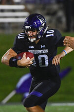 "FILE - In this Sept. 15, 2018, file photo, Northwestern quarterback TJ Green (10) runs against Akron during the second half of an NCAA college football game in Evanston, Ill. As he listened to his team's introduction during last month's Big Ten Kickoff Luncheon, Northwestern coach Pat Fitzgerald was a bit stunned by what he heard.  ""Clayton Thorson leaves as the winningest quarterback in Northwestern history,"" the Big Ten Network's Rick Pizzo said, reading from a script. ""But he'll be replaced by five-star Clemson transfer Hunter Johnson.""  That was news to Fitzgerald, who said the competition for starting quarterback at the beginning of fall camp was wide open with Hunter, senior TJ Green and junior Aidan Smith being the main contenders.  (AP Photo/Matt Marton)"